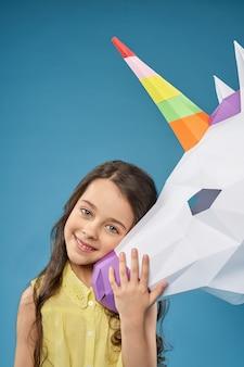 Menina bonita brincando com unicórnio de papel e rindo