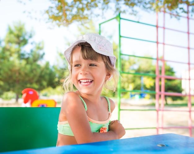 Menina bonita brincando de boneca ao ar livre enquanto relaxa na praia em um dia quente de verão