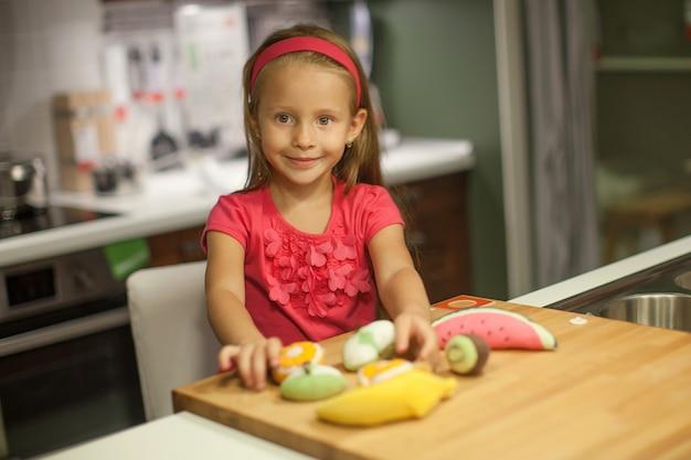 Menina bonita brincando na cozinha com frutas e legumes