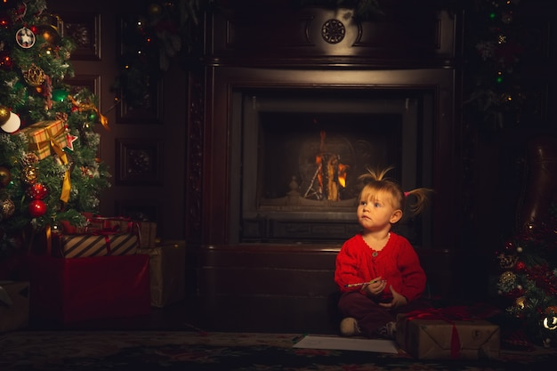 Menina bonita brincando na sala de estar perto da árvore de natal.