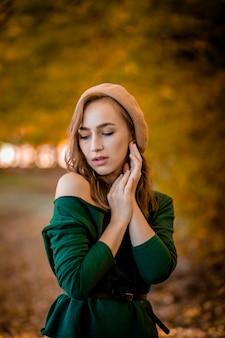 Menina bonita, caminhando ao ar livre no outono. a menina de sorriso recolhe as folhas amarelas no outono. jovem, aproveitando o clima de outono.