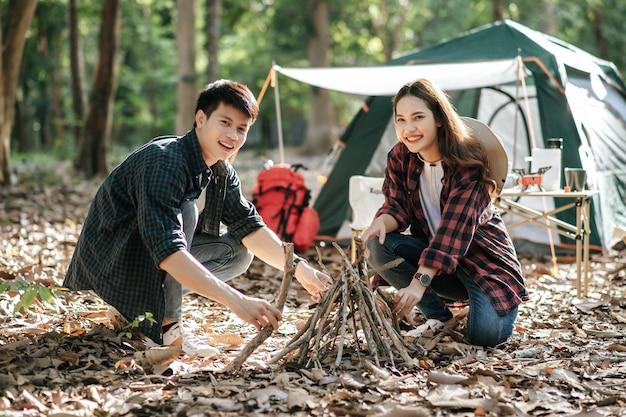 Menina bonita campista preparando lenha com o namorado para iniciar uma fogueira. jovem casal de turistas ajudando a colher galhos e montá-los na frente de uma barraca de acampamento