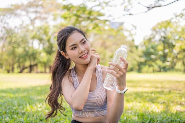 Menina bonita cansada do exercício. linda garota bebendo água com sede.