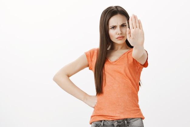 Menina bonita carrancuda e séria diz para parar, o suficiente ou não. mulher estende o braço em gesto de proibição