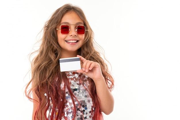 Menina bonita caucasiana com cartão de plástico, imagens isoladas na parede branca