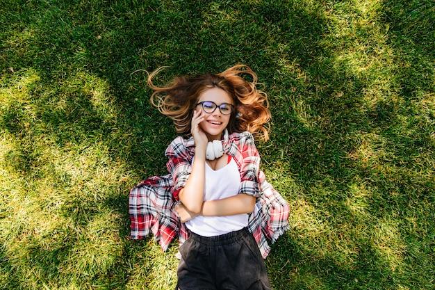 Menina bonita caucasiana de óculos deitada no gramado verde. retrato ao ar livre aéreo de uma jovem agradável relaxando no parque.