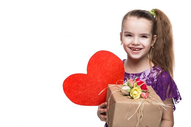 Menina bonita caucasiana em vestido de renda roxa, segurando uma caixa com um presente decorado com flores. tiro no estúdio em fundo branco isolado