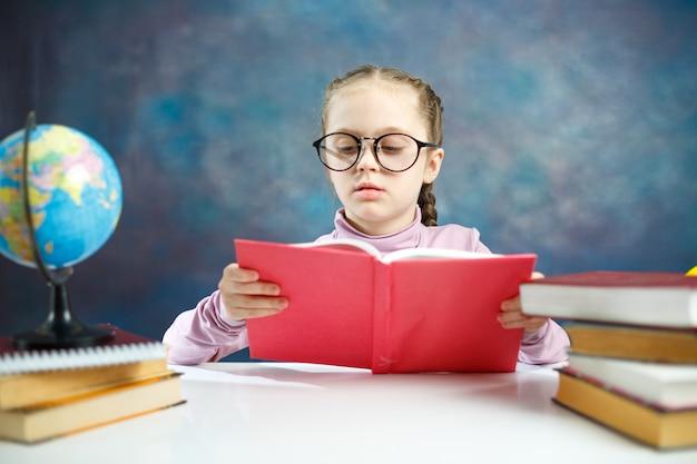 Menina bonita caucasiana estudante primário lendo um livro