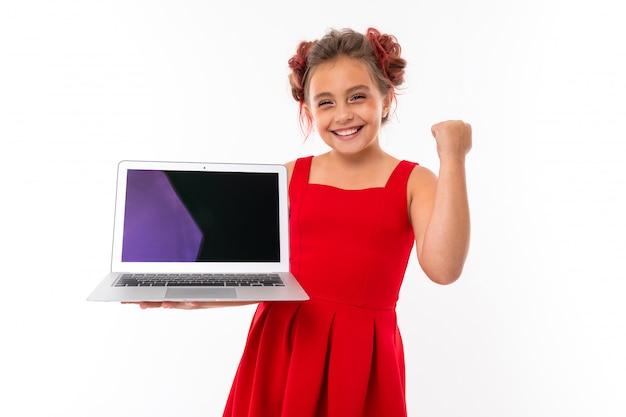 Menina bonita caucasiana no vestido vermelho mantém laptop isolado na parede branca