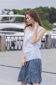 Menina bonita caucasiana, passando o tempo no cais em frente a iates de luxo em uma blusa leve e saia azul dividida.
