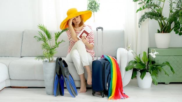 Menina bonita chateada com um chapéu amarelo fica em casa e planeja uma viagem de férias. mala e nadadeiras para mergulho.