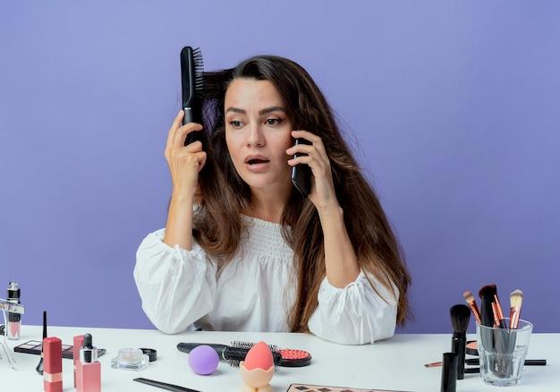 Menina bonita chocada sentada à mesa com ferramentas de maquiagem, penteando o cabelo e falando ao telefone, olhando para o lado isolado na parede roxa
