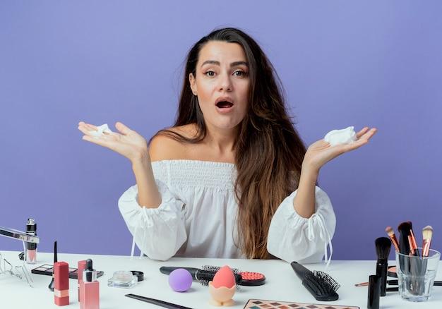 Menina bonita chocada sentada à mesa com ferramentas de maquiagem segurando mousse de cabelo isolada na parede roxa