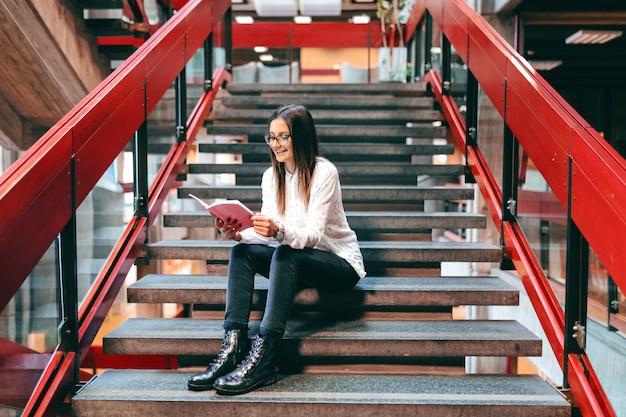 Menina bonita colagem sentado na escada, segurando o notebook