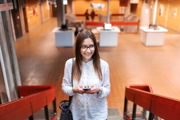 Menina bonita colagem sorridente subindo as escadas e usando telefone inteligente