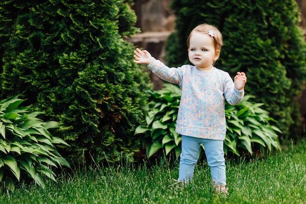 Menina bonita com a flor em sua cabeça ao ar livre no dia ensolarado.