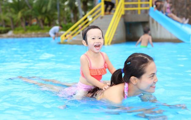 Menina bonita com a mãe dela brincando na piscina ao ar livre