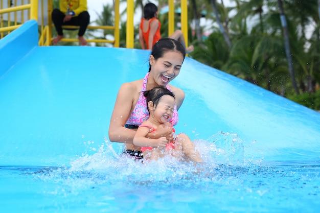 Menina bonita com a mãe dela deslizando na piscina ao ar livre