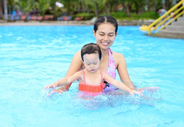 Menina bonita com a mãe na piscina ao ar livre