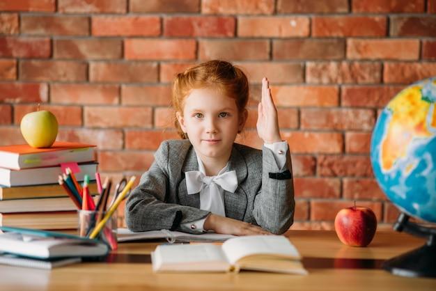 Menina bonita com a mão levantada, sentado à mesa com livros didáticos, maçãs e globo.