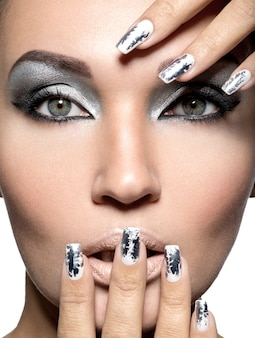 Menina bonita com a maquiagem prata e as unhas de metal.