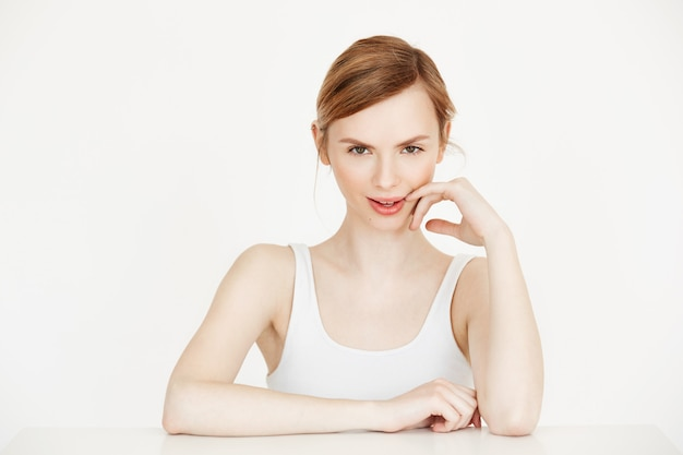 Menina bonita com a pele limpa saudável, sorrindo, tocando o rosto, sentado à mesa. tratamento facial.