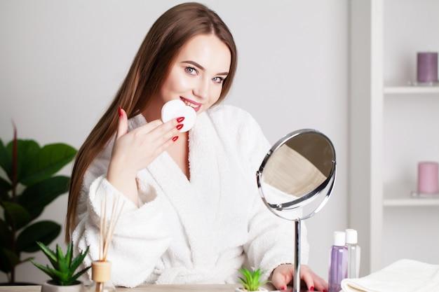 Menina bonita com a pele saudável, fazendo maquiagem