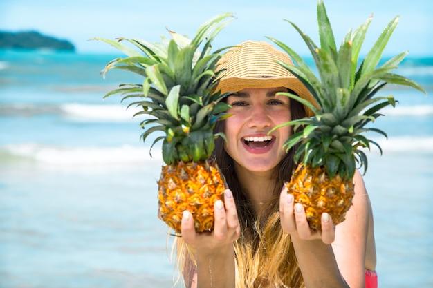 Menina bonita com abacaxi em uma praia exótica, um clima feliz e um sorriso lindo