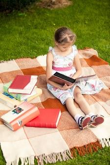 Menina bonita com álbum de fotos sentada na manta no parque