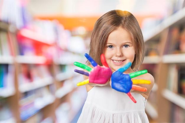 Menina bonita com as mãos pintadas com tinta colorida