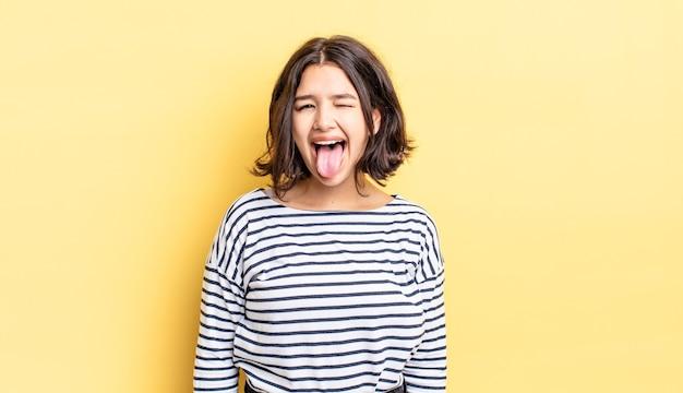 Menina bonita com atitude alegre, despreocupada e rebelde, brincando e mostrando a língua, se divertindo