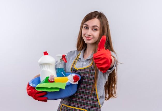Menina bonita com avental e luvas de borracha segurando a bacia com ferramentas de limpeza sorrindo mostrando os polegares para cima