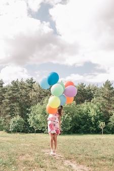 Menina bonita com balões correndo no gramado verde