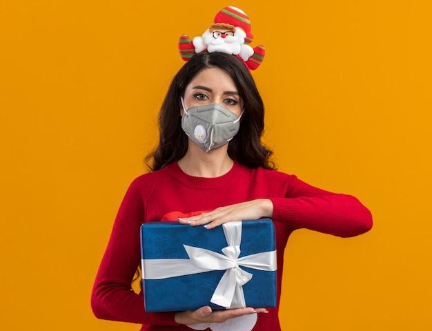 Menina bonita com bandana de papai noel e suéter com máscara protetora segurando um pacote de presente isolado na parede laranja