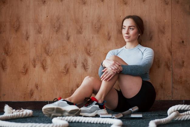 Menina bonita com belo corpo. jovem esportiva fazendo exercícios na academia pela manhã