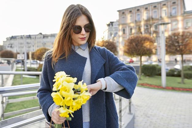Menina bonita com buquê de flores amarelas da primavera