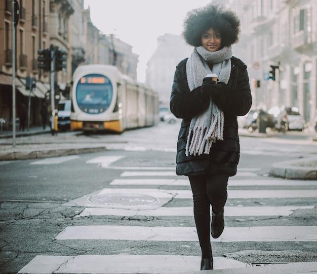 Menina bonita com cabelo afro, andando na rua