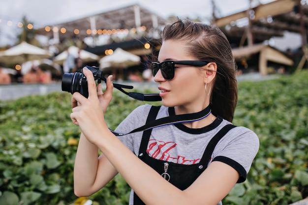 Menina bonita com cabelo castanho, tirando fotos no parque em tempo ventoso. foto ao ar livre de fotógrafa caucasiana, passando um tempo na cidade durante o trabalho.