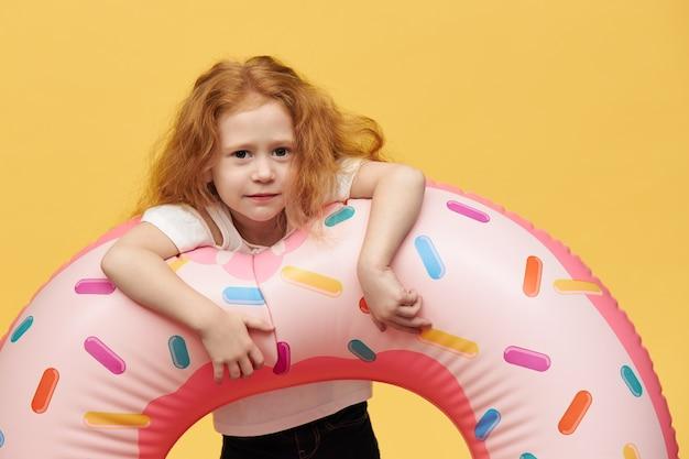 Menina bonita com cabelo comprido abraçando um círculo inflável de natação