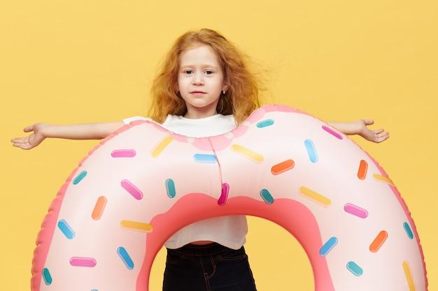 Menina bonita com cabelo comprido e círculo inflável de natação