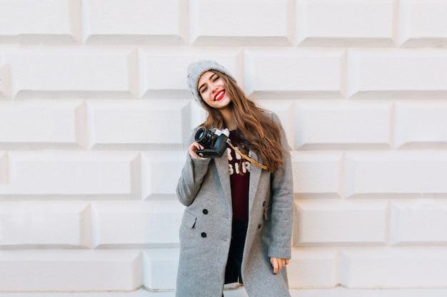 Menina bonita com cabelo comprido e lábios vermelhos no casaco cinza e chapéu de malha na parede cinza. ela segura a câmera e sorrindo.