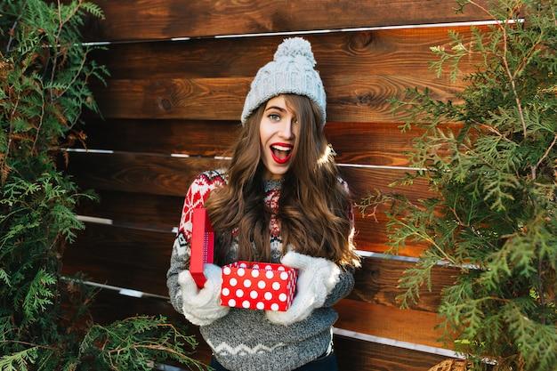 Menina bonita com cabelo comprido em roupas de inverno na madeira. ela segura o presente de natal em luvas e parece surpresa.