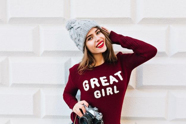 Menina bonita com cabelo comprido em suéter marsala na parede cinza. ela usa chapéu de malha, segura a câmera nas mãos e sorrindo.