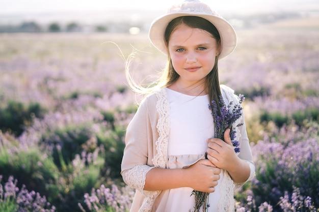 Menina bonita com cabelo comprido em um vestido de linho e um chapéu com um buquê de lavanda em pé em um campo de lavanda