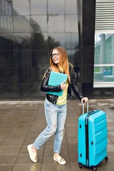 Menina bonita com cabelo comprido está andando com a mala do lado de fora no aeroporto. ela usa uma jaqueta preta com jeans e segura o laptop. ela parece feliz.