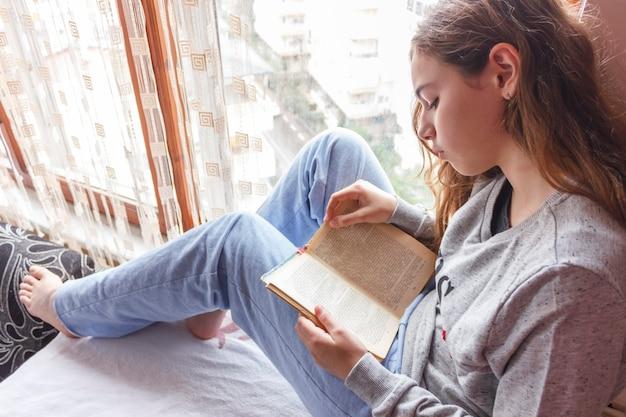 Menina bonita com cabelo comprido, lendo um livro perto da janela