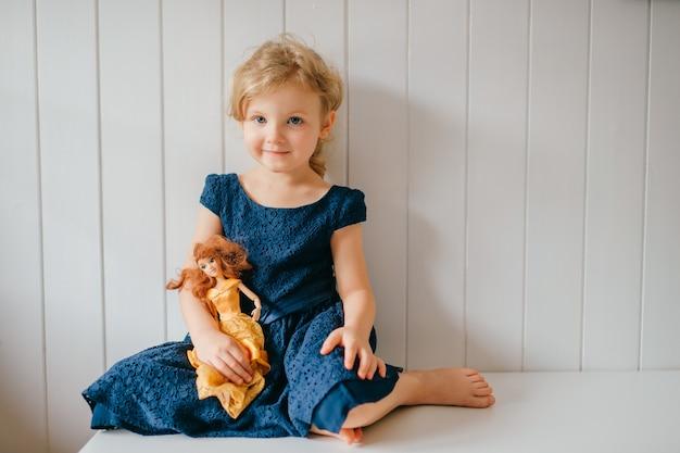 Menina bonita com cabelo curto loiro em um vestido azul segurando seu adorável brinquedo barbie, sentada no quarto do bebê e sorrindo