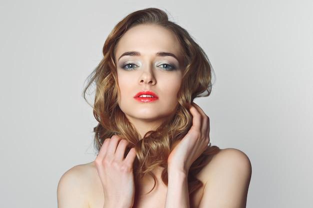 Menina bonita com cabelo encaracolado, leve e arejado make-up, lábios cor de rosa.