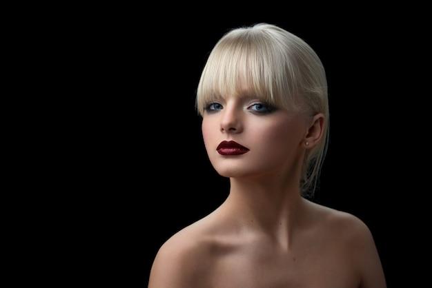 Menina bonita com cabelo loiro e noite compõem a olhar para a câmera.