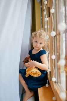 Menina bonita com cabelo loiro em um vestido azul segurando seu adorável brinquedo e está sentada no quarto do bebê em um parapeito da janela e sorri
